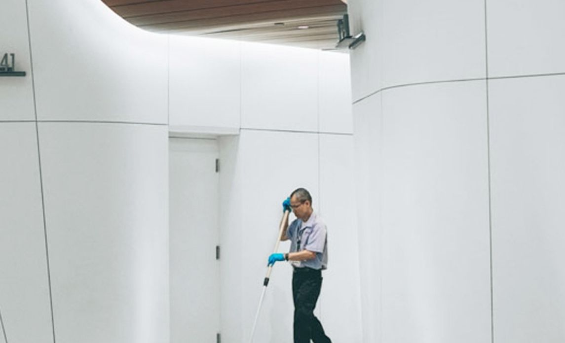 Cleaning professional in bright hallway