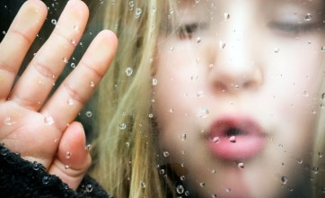 Child by the window with condensation
